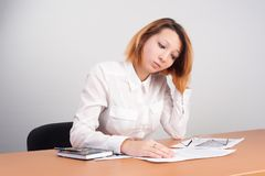 Business analyst woman working. Caucasian businesswoman sitting at desk in casual clothes and analyzing sales statistics royalty free stock image