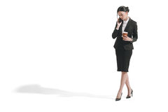 Caucasian businesswoman talking on smartphone while holding paper coffee cup Royalty Free Stock Photography