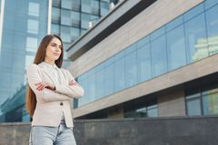 Caucasian businesswomanoutdoors in smart casual. Portrait of thoughtful confident caucasian businesswoman against modern glass office center background. Pensive Royalty Free Stock Photography