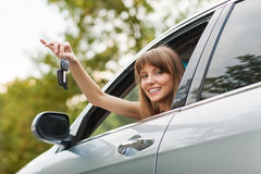 Caucasian car driver woman smiling. Showing new car keys and car Royalty Free Stock Image