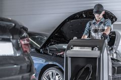 Mechanic with Jumper Booster. Caucasian Car Mechanic in His 30s with Heavy Duty Commercial Grade Jumper Booster Inside Auto Service Center royalty free stock image