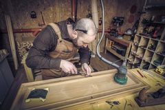 Carpenter at work. Caucasian carpenter at work in his workshop royalty free stock photography