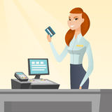 Caucasian cashier holding a credit card. Caucasian smiling cashier standing at the checkout and holding a credit card. Young cheerful cashier making payment by Stock Images