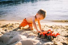 Caucasian child boy playing toy red tractor, excavator on a sandy beach by the river in red shorts at sunset day stock images