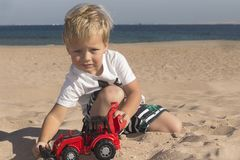 Caucasian child boy playing toy red tractor, excavator on a sandy beach at sunny day. stock photo