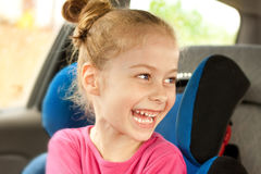Caucasian child girl laughing while traveling in a car seat stock images