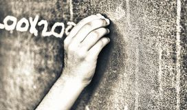 Caucasian child hand writing at chalkboard.  Royalty Free Stock Photos