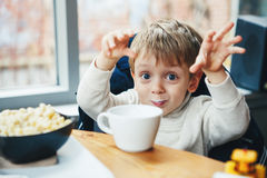 Caucasian child kid boy drinking milk from white cup eating breakfast lunch Stock Images