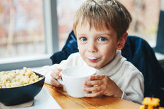 Caucasian child kid boy drinking milk from white cup eating breakfast lunch. Portrait of cute adorable Caucasian child kid boy drinking milk from white cup royalty free stock photos