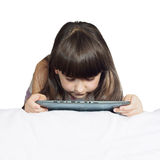 Caucasian child kid girl sister lying on the bed with tablet pc isolated Royalty Free Stock Photography