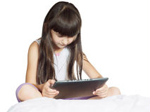 Caucasian child kid girl sister sitting on the bed with tablet p Royalty Free Stock Image