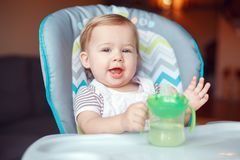 Caucasian child kid girl sitting in high chair drinking water from spill-proof sippy cup