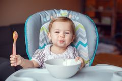 Caucasian child kid girl sitting in high chair eating cereal with spoon. Portrait of cute adorable Caucasian child kid girl sitting in high chair eating cereal stock photography