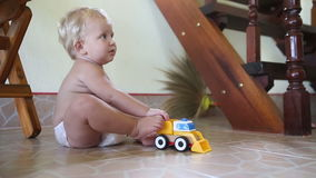 Caucasian child plays with cars on the floor near the stairs stock footage