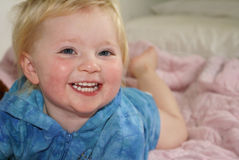 Caucasian child's closeup smile. Small girl lying on bed with closeup of laughing explression Royalty Free Stock Image