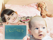 Caucasian child sister holding chalkboard and baby brother face Royalty Free Stock Photos