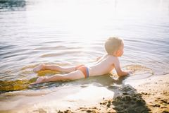 A Caucasian child of three years in red swimming trunks lies on his stomach in the water near the river bank of a sandy beach. Lea royalty free stock photography