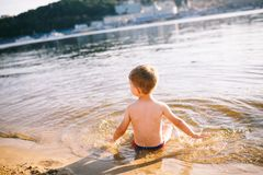 A Caucasian child of three years in red swimming trunks lies on his stomach in the water near the river bank of a sandy beach. Lea. Rns to swim with a smile on Stock Image
