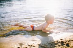 A Caucasian child of three years in red swimming trunks lies on his stomach in the water near the river bank of a sandy beach. Lea. Rns to swim with a smile on Stock Photos