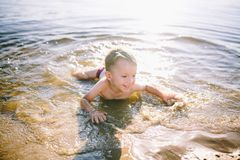 A Caucasian child of three years in red swimming trunks lies on his stomach in the water near the river bank of a sandy beach. Lea. Rns to swim with a smile on Stock Photo