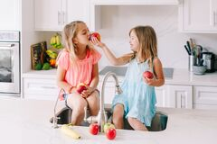 Free Caucasian Children Girls Eating Sharing Fresh Fruits Sitting In Kitchen Sink. Happy Family Sisters Siblings Having Snack. Organic Royalty Free Stock Photo - 173777845