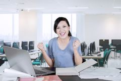 Caucasian college student celebrating her success. Picture of Caucasian female college student celebrating her success while lifting hands in the classroom royalty free stock photography