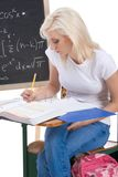 Caucasian college student woman studying math exam. High school or college female student sitting by the desk at math class. Blackboard with complicated advanced Stock Photo
