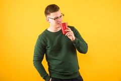 Portrait of young handsome confident guy in green sweater holding red plastic cup on yellow background stock photo