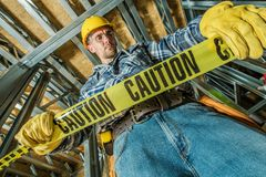 Worker with Caution Tape. Caucasian Construction Worker in His 30s with Caution Tape. Construction Site Safety royalty free stock photo