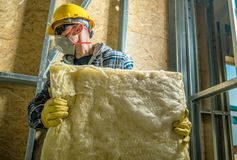 Worker with Wool Insulation. Caucasian Construction Worker Wearing Safety Mask Moving Pieces of Mineral Wool Insulation stock photography