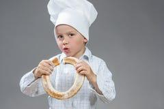 Caucasian contentissimo Little Boy che mangia il panino fresco della ciambella Posando nella cottura del cappello Immagine Stock