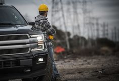 Contractor Field Work Job. Caucasian Contractor Field Work Job. Worker and His Pickup Truck. Countryside Remote Location with High Voltage Poles in the Stock Photography