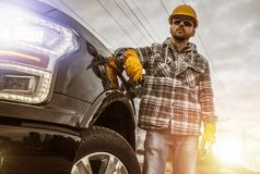 Contractor and His Pickup Truck. Caucasian Contractor in His 30s and His Modern Heavy Duty Pickup Truck For Heavy Loads Stock Photo