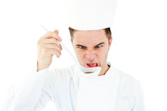 Caucasian cook tasting a soup doing a grimace Royalty Free Stock Images
