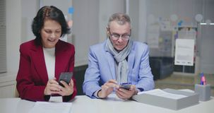 Caucasian couple in ages sitting in modern bank office. And waiting for bank manager using smartphones stock video