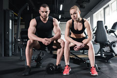 Caucasian couple of athletes training at gym. Young caucasian couple of athletes training at gym Royalty Free Stock Photography