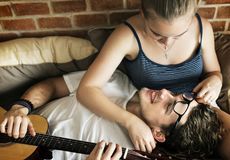 Caucasian couple on the bed, man playing a guitar royalty free stock photo