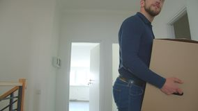 Caucasian couple brings cardboard box into a new house and looking around being happy and excited.