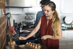 Caucasian couple cooking eggs in the kitchen royalty free stock images