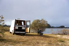 Free Caucasian Couple Eating Breakfast On A Lake With A Camper Van Living Van Life Social Distancing On A Dam In Portugal Stock Photos - 213910483