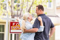 Caucasian Couple Facing and Pointing at Sold Real Estate Sign royalty free stock photos