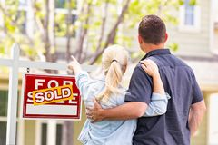 Caucasian Couple Facing and Pointing to Front of Sold Real Estate Sign and House royalty free stock image