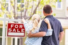 Caucasian Couple Facing and Pointing to For Sale Real Estate Sign royalty free stock photography