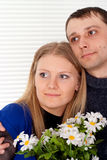 Caucasian couple with flowers stands Royalty Free Stock Image