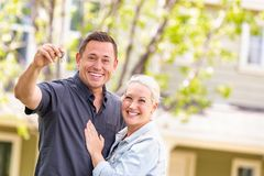 Caucasian Couple in Front of House with Keys.  stock photography