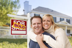 Caucasian Couple in Front of New House and Sold Sign. Affectionate Happy Couple in Front of New House and Sold For Sale Real Estate Sign royalty free stock photos