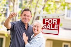Caucasian Couple in Front of For Sale Real Estate Sign and House royalty free stock image