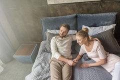 Caucasian couple holding hands and relaxing on bed at home Stock Images