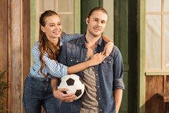 Caucasian couple holding soccer ball and hugging Royalty Free Stock Image