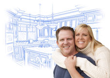 Caucasian Couple Hugging with Custom Kitchen Drawing Behind. Happy Couple Hugging with Custom Kitchen Drawing Behind on White royalty free stock photography
